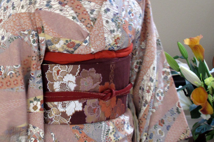 A cord tied in a square knot holds the thick belt around the waist of a kimono.