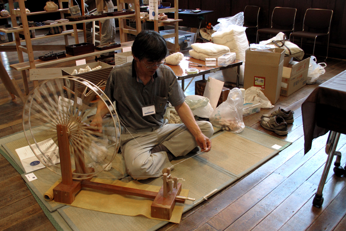 A man demonstrates cotton spinning on a wheel at Craft Fair Matsumoto