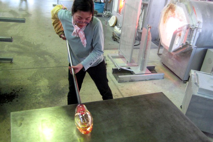 Nitta Yoshiko rolls a gather of glass on a marver in her Tokyo hot shop